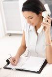Office girl taking notes. Into organizer, holding landline phone, sitting at desk, smiling Stock Images
