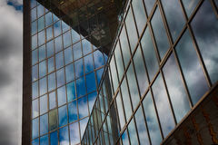 Office glass building in abstract. Office skyscraper towards a clouded sky. Glass building in abstract royalty free stock image