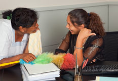 Office gossip. Cleaning woman and secretary talking gossip in the office Stock Photos