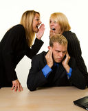 Office gossip. One business man with hands covering hears sitting at desk with two woman coworkers talking behind his back Royalty Free Stock Images