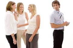 Office Gossip. Three businesswoman gossip behind a male colleagues back Stock Photo