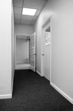 Office hallway. Looking down office building hallway towards tiled entry Stock Photos