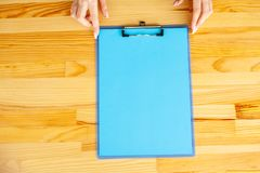 Office Hand Holding a Folder with a Blue Color Paper on the Background of the Wooden Table. Copyspace. Place for Text. Office Hand Holding a Folder with a Blue royalty free stock photography
