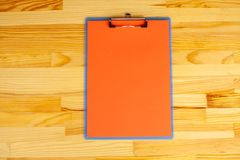 Office Hand Holding a Folder with a Red Color Paper on the Background of the Wooden Table. Copyspace. Place for Text. Office Hand Holding a Folder with a Red stock images