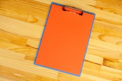 Office Hand Holding a Folder with a Red Color Paper on the Background of the Wooden Table. Copyspace. Place for Text. Office Hand Holding a Folder with a Red royalty free stock photos