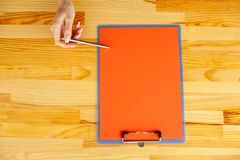 Office Hand Holding a Folder with a Red Color Paper and Pen on the Background of the Wooden Table. Copyspace. Place for Text. Office Hand Holding a Folder with royalty free stock photography