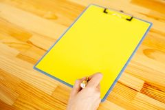Office Hand Holding a Folder with a Yellow Color Paper and Pen on the Background of the Wooden Table. Copyspace. Place for Text. Office Hand Holding a Folder stock photos