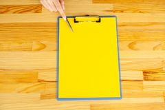 Office Hand Holding a Folder with a Yellow Color Paper and Pen on the Background of the Wooden Table. Copyspace. Place for Text. Office Hand Holding a Folder stock image