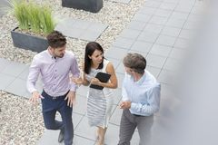 High angle view of professionals discussing while walking at office terrace stock photography