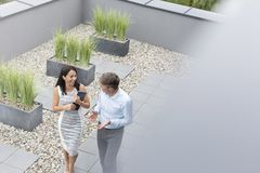 High angle view of smiling professionals talking at office terrace stock photography