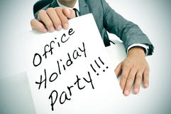 Office holiday party. A man wearing a suit sitting in a desk holding a signboard with the text office holiday party written in it stock images
