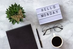 Office or home table desk. Lightbox text hello monday Black notepad, cup of coffee, succulent, glasses on marble background royalty free stock photo