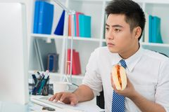 Office hot-dog. Busy office guy eating a hot-dog instead of a proper lunch royalty free stock images