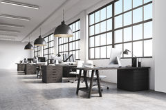 Office interior with massive ceiling lamps. Office interior with a row of dark wood tables standing under large windows. Massive ceiling lamps. Computers. 3d Royalty Free Stock Images