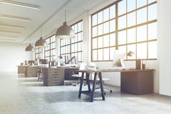 Office interior with massive ceiling lamps, toned. Office interior with a row of dark wood tables standing under large windows. Massive ceiling lamps. Computers Royalty Free Stock Photo