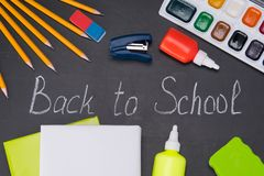 Office items laid out on a black Board with the inscription, forward to school stock photos