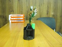 Office items. Office table, on the table stand for pens with a sprig of winter spruce, a stack of papers royalty free stock photography