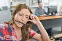 Office lady holding pen between her teeth Stock Photography
