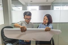 Office lady showing data on project drawing to her colleague stock photography