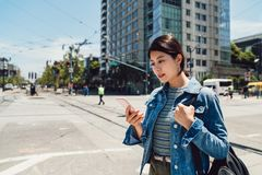 Office lady walking on the busy urban road. Asian office lady going to work walking on the busy urban road using cellphone replying message texting. young royalty free stock photo