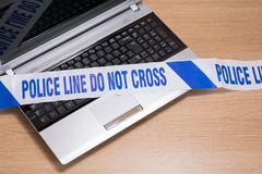 Office laptop keyboard and police crime scene tape. An open office computer laptop on a plain timber desk with police crime scene tape across the keyboard Stock Photos