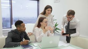 In office leader gives task to team in which is an African-American man. International group of four men and women in strict suits discuss topic by time of stock video footage
