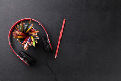 Office leather desk with pencils and headphones Stock Images