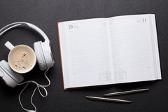 Office leather desk table with notepad, headphones and coffee Royalty Free Stock Photo