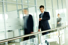 Office life. Businessmen looking at watch with walking people on background royalty free stock photography