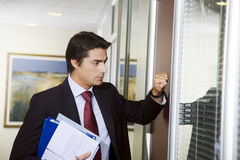 Office life. Young employee knocking on his boss door Stock Photography