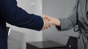 Office life concept. Close up of two unrecognizable male and female business partners shaking hands. Shot in 4 k. Office life concept. Close up of two stock video footage