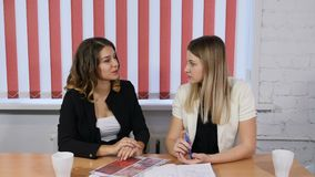 Office life concept. Two pretty business women discussing future plans, ideas. Smilie. Pleasant emotions. Shot in 4k. Office life concept. Two pretty business stock footage