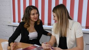 Office life concept. Two pretty business women discussing future plans, ideas. Smilie. Pleasant emotions. Shot in 4k. Office life concept. Two pretty business stock video footage