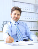 Office life - friendly businessman. Writing Royalty Free Stock Photo
