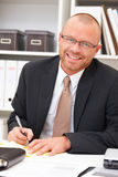 Office life - friendly businessman writing Stock Photo