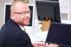 Office life - Happy businessman using a laptop Stock Photo