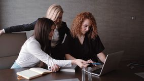 Office life. Three businesswomen working together on a laptop in a modern office stock video