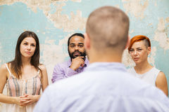 Office life. Young men speaks to other young people by grunge wall royalty free stock photography