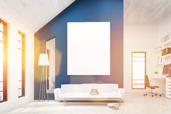 Office lounge area toning. Lounge area in office interior with blank whiteboard on blue concrete wall, floor lamp, couch, coffee table with decorative vase Stock Images