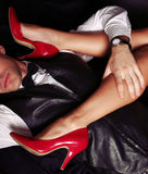 Office love story. woman's legs in red shoes. Fashion studio photo of couple. office love story. woman's legs in red shoes in man's hands Royalty Free Stock Image