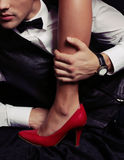 Office love story. woman's legs in red shoes. Fashion studio photo of couple. office love story. woman's legs in red shoes in man's hands Stock Photos