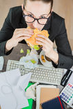 Office lunch. Office worker eating a burger at the workplace. Confusion untidy desktop. Top view Royalty Free Stock Photography