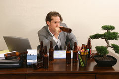 Office Lush. Business man at desk with empty beer bottles stock photos