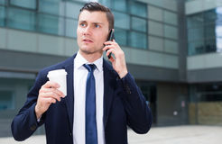 Office male worker is drinking coffee and talking phone. Outside the office Royalty Free Stock Images