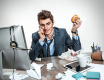 Office man calling during his breakfast. Modern office man calling during his breakfast at working place Royalty Free Stock Photos