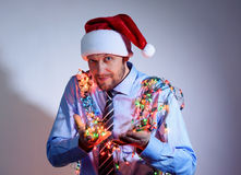 Office man in a Santa Claus red cap with colored garlands Stock Photography