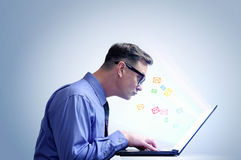 Office man in shirt and glasses sitting at a laptop Stock Photo