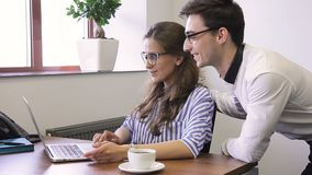 In office man and woman with glasses smiling at desk in front of laptop. Smiling staff have fun while watching video during a working break and click on stock video footage