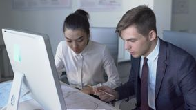 In office man and woman are sitting at computer and discussing project. 4k. Concept: two people, business plan, modern computer stock video footage
