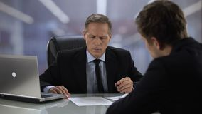 Office manager giving new project plan to boss, company head pleased with offer stock footage
